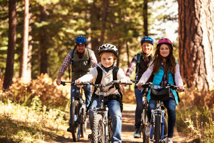 Family mountain biking on forest trail, front view