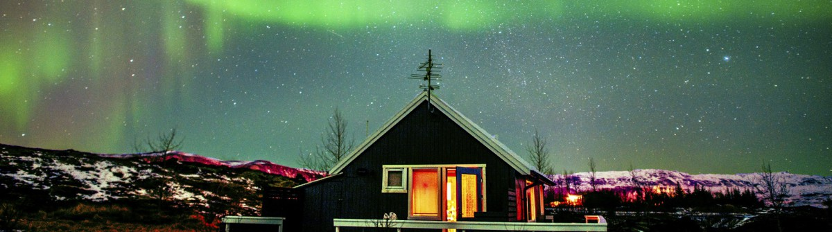 Northern Lights visible above small cabin in Iceland iStock_000066132119_Large