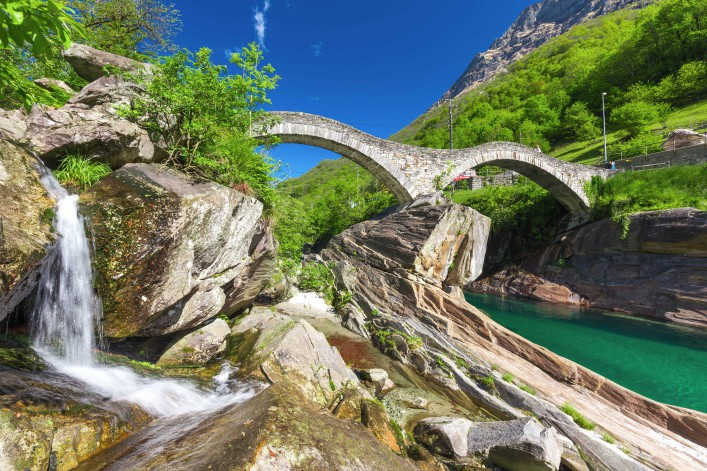 Double arch stone bridge at Ponte dei Salti with waterfall, Lavertezzo, Verzascatal, Canton Tessin shutterstock_430079833-2