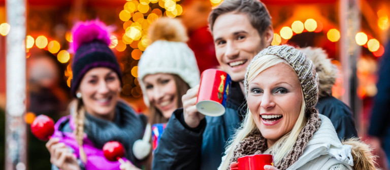 Friends drinking mulled wine and eating crystalized appkes on German Christmas Market shutterstock_227463559-2