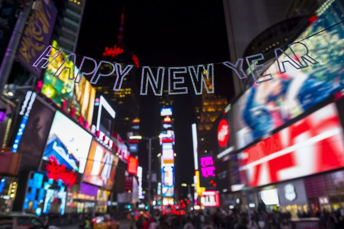 Glittery Happy New Year message strung across the flashing lights of Times Square, New York City shutterstock_543169873