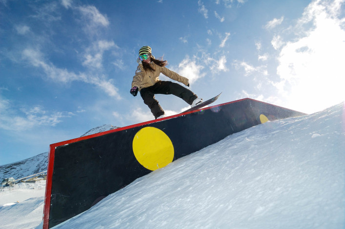 young snowboarder woman jibbing