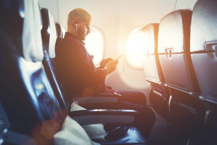 Mann im Flugzeug_flight_man_smartphone_shutterstock_399955888