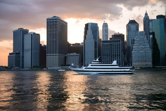 New York City skyline at sunset cruise ship with tourists