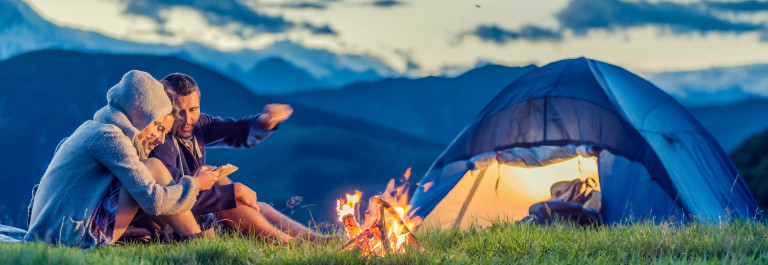Three friends camping on mountain at sunset