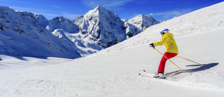 Ski, skier on ski run – woman skiing downhill, winter sport