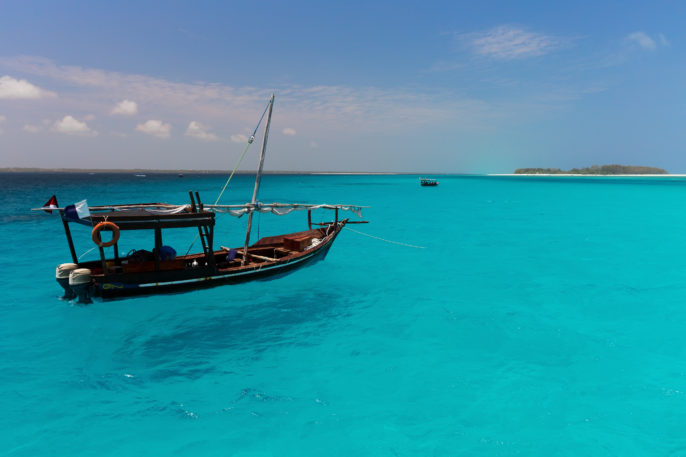 Dhow boat on the amazing turquoise water in the Indian ocean next to Mnemba atoll, Zanzibar, Tanzania_shutterstock_176985731