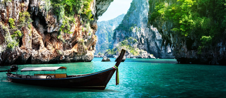 long boat and rocks on railay beach in Krabi, Thailand shutterstock_125319602-2