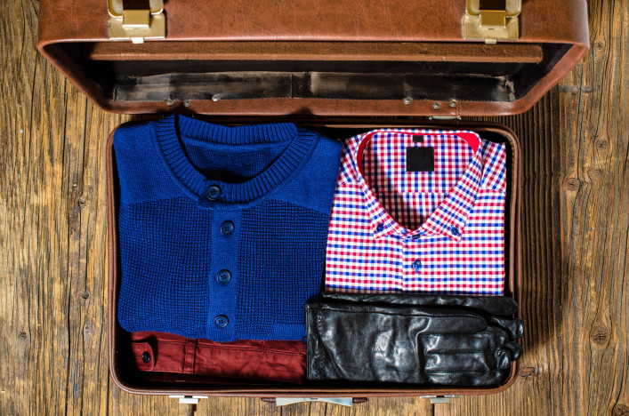 Open travel suitcase with casual man clothes