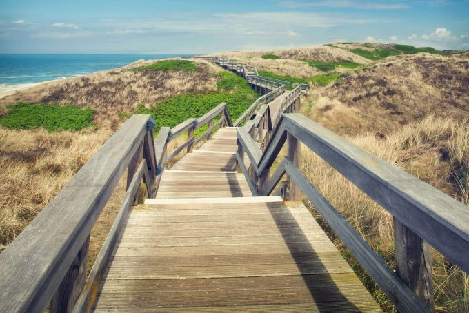 A wooden walking path on the island of Sylt, sunny summer day with blue sky_shutterstock_192316313_klein