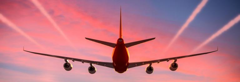 Airplane flying in the sky at sunset with vapor trails