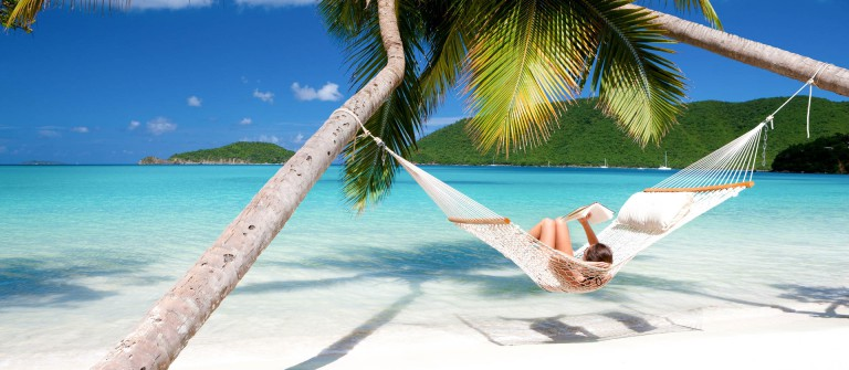 woman reading a book in hammock at the Caribbean beach