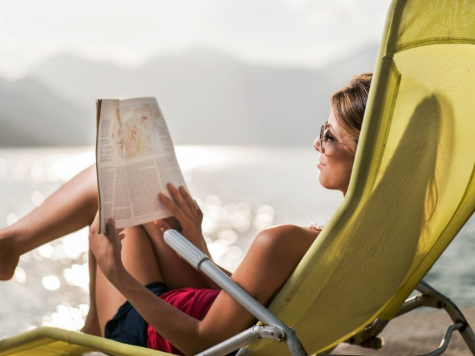 Smiling woman reading a magazine in deck chair.