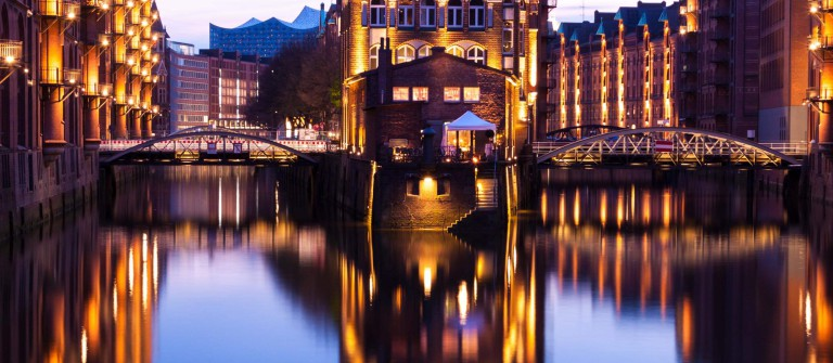 Speicherstadt during twilight in Hamburg, Germany, reflection of lights and buildings on water in canal_shutterstock_418820773