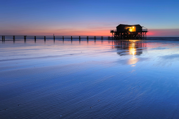 Stilt house and Jetty on the beach at sunset, St. Peter Ording, Germany_shutterstock_496356016_klein
