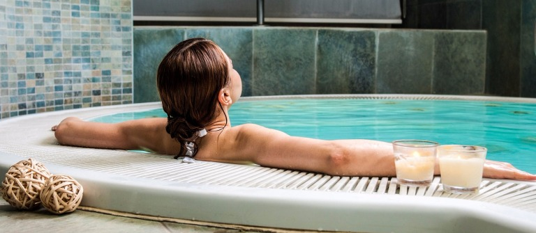 Young woman relaxing at the edge of a hot pool at spa center shutterstock_102272116-2