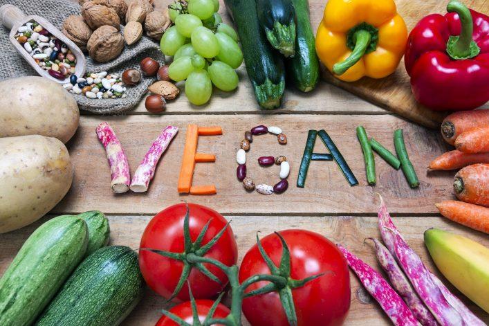 Auf einem Holztisch steht vegan mit Gemüse geschrieben.
