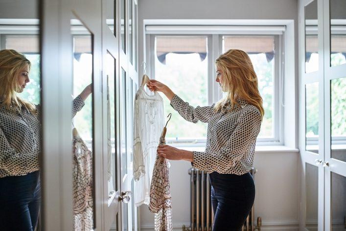 Frau steht vor einem vollen Kleiderschrank