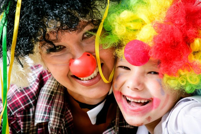 Eine verkleidete Mutter und ihr verkleidetes Kind lachen an Karneval in die Kamera.