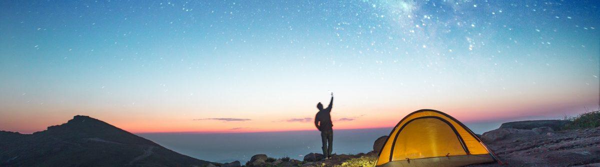 Ein Mann steht vor einem Sternenhimmel neben einem Zelt