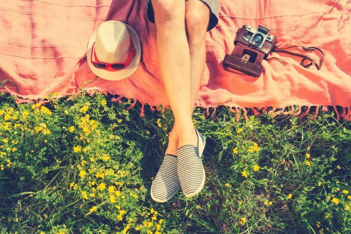 Eine Frau liegt mit einer Decke auf einer Wiese im Sommer.