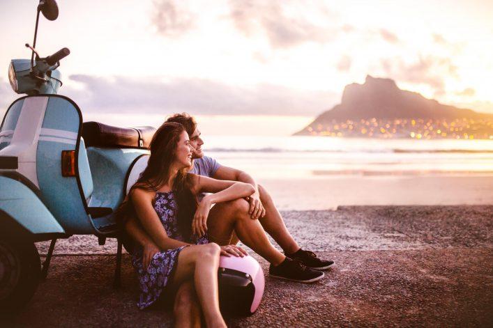 Zwei Freunde sitzen am Strand und planen ihre nächste Reise