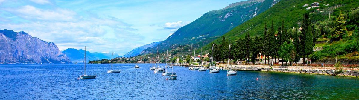 Yacht ship and Italian turquoise translucent Lake Garda paradise, Malcesine