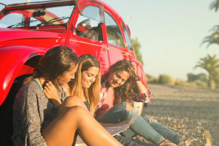 Mädels planen vor dem Auto ihren Roadtrip