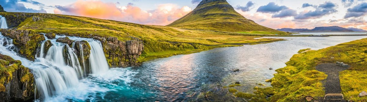 Idyllic waterfall sunrise cloudscape beside mountain peak panorama Kirkjufell Iceland
