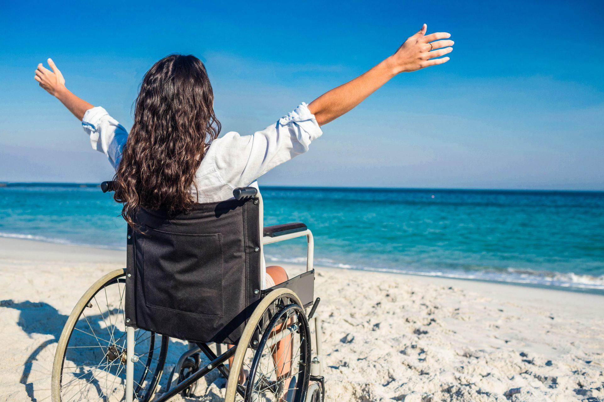 Eine Frau sitzt im Rollstuhl am Meer