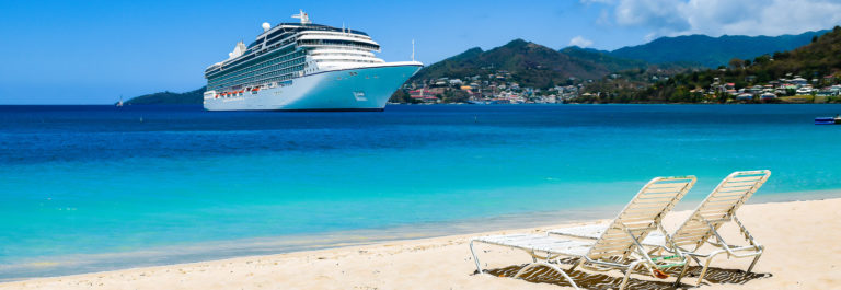 Cruise ship in Caribbean Sea with beach chairs on white sandy beach shutterstock_549644014-2