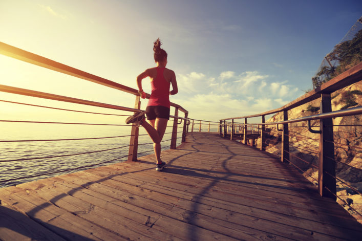 young fitness woman running on seaside wooden boardwalk