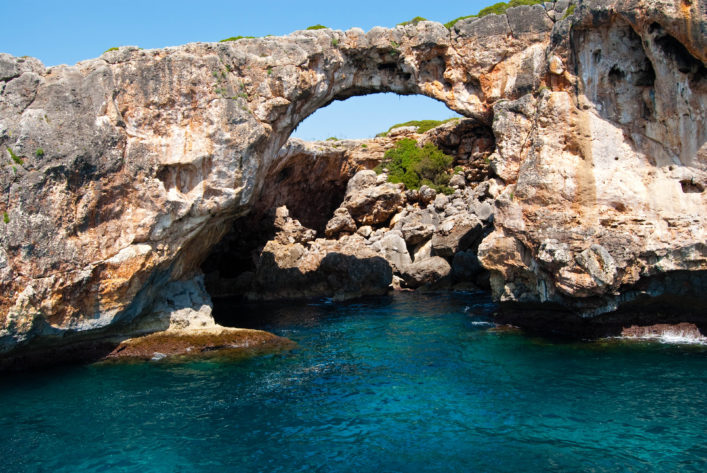 Natural arch and the grotto at Cala Antena, Majorca island, Spain shutterstock_54519322-2