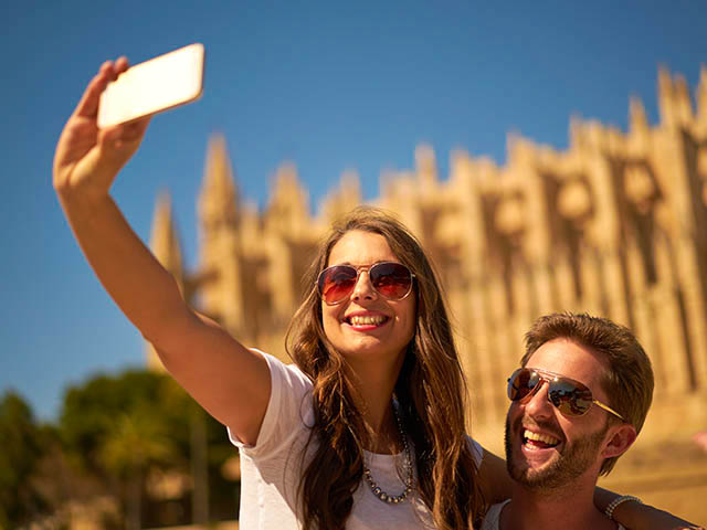 Couple taking selfie in front of cathedral iStock-612635642