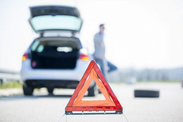 Ein Mann hat eine Panne mit seinem Auto und stellt ein Warndreieck auf
