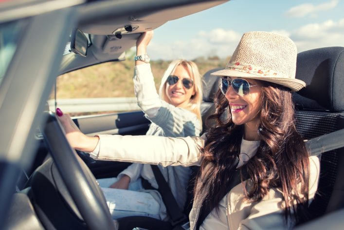Zwei Freundinnen sitzen im Mietwagen