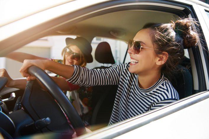 Zwei Freundinnen lachen im Auto