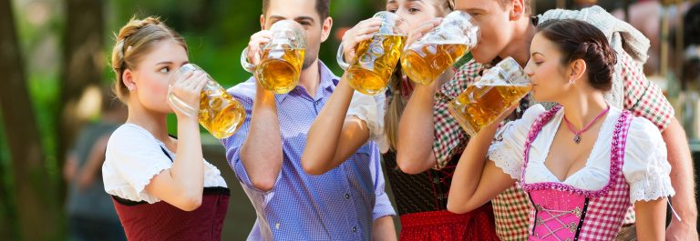 In Beer garden in Bavaria, Germany – friends in Tracht, Dirndl and Lederhosen and Dirndl standing in front of band_shutterstock_138936287