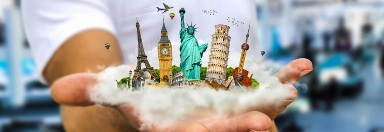 Young man holding a cloud full of famous monuments of the world in his hands shutterstock_386614045-2