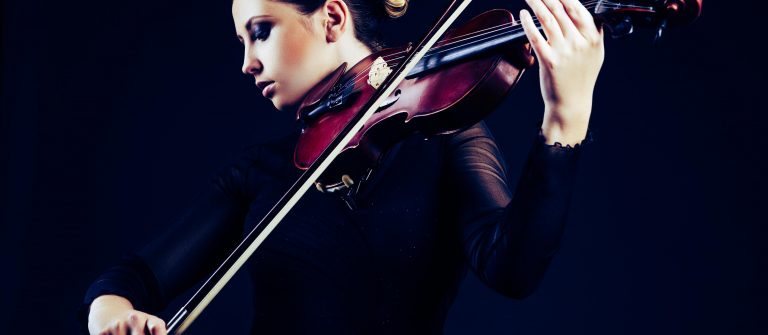 Beautiful young woman playing violin over black