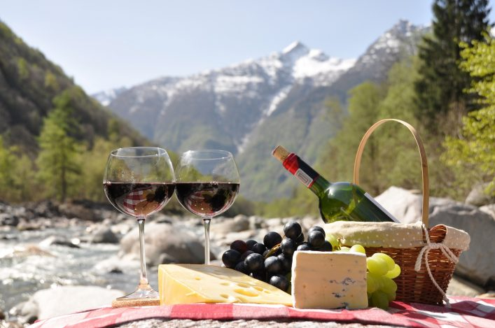 Red wine, cheese and grapes served at a picnic. Verzasca valley, Switzerland shutterstock_75126337