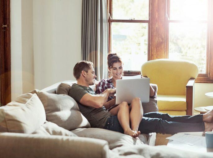 Ein Paar sitzt auf dem Sofa und füllt einen ESTA Antrag aus