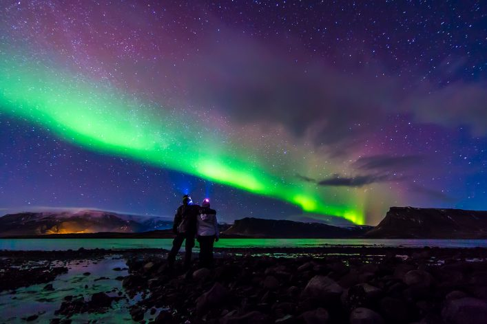 Young Couple hugged under Northern lights Aurora Borealis in Iceland