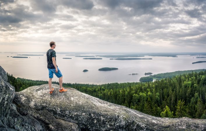 Hiker standing top of the hill front of beautiful idyllic landscape in Koli, Finland