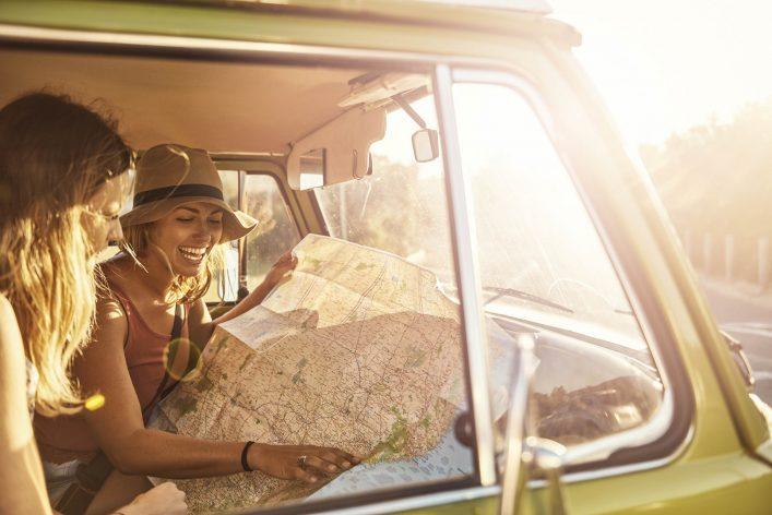 Zwei Frauen sitzen im Auto und lesen eine Karte.