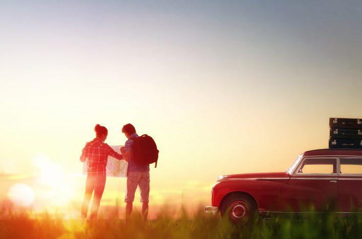 Eine Frau und ein Mann schauen sich bei Sonnenuntergang eine Karte an.