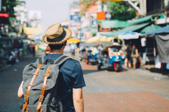 Ein Mann wandert mit seinem Rucksack durch ein fremdes Land.