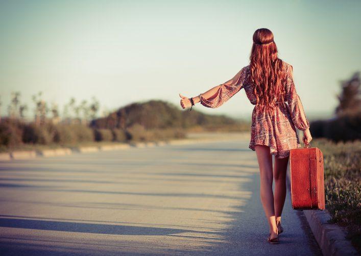 Eine junge Frau reist per Anhalter.