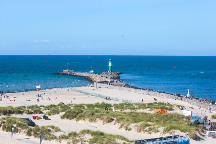 Beautiful summer vibrant view of Warnemunde, Rostock, Germany, popular german seaside resort, with beach, seashore and lighthouse shutterstock_709358101