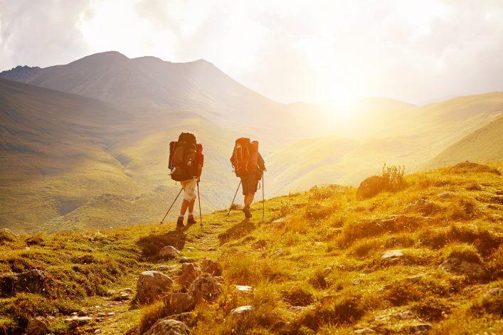 Wanderer laufen in Armeniens Hügellandschaft der untergehenden Sonne entgegen.